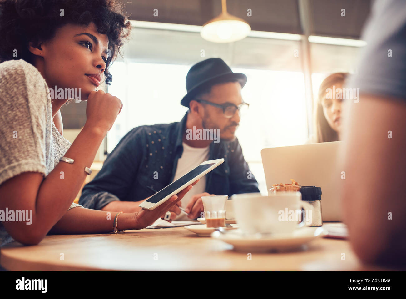 Close up portrait of  african woman with digital tablet and people in background at a cafe table. Young friends - Stock Image