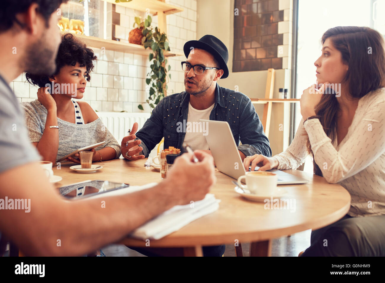Portrait of young friends sitting in a coffee shop and discussing. Creative people meeting at a cafe. - Stock Image