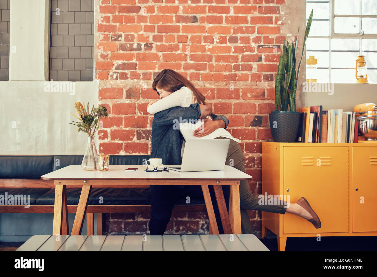 Portrait of man and woman embracing each other at a cafe, couple meeting in a coffee shop. - Stock Image