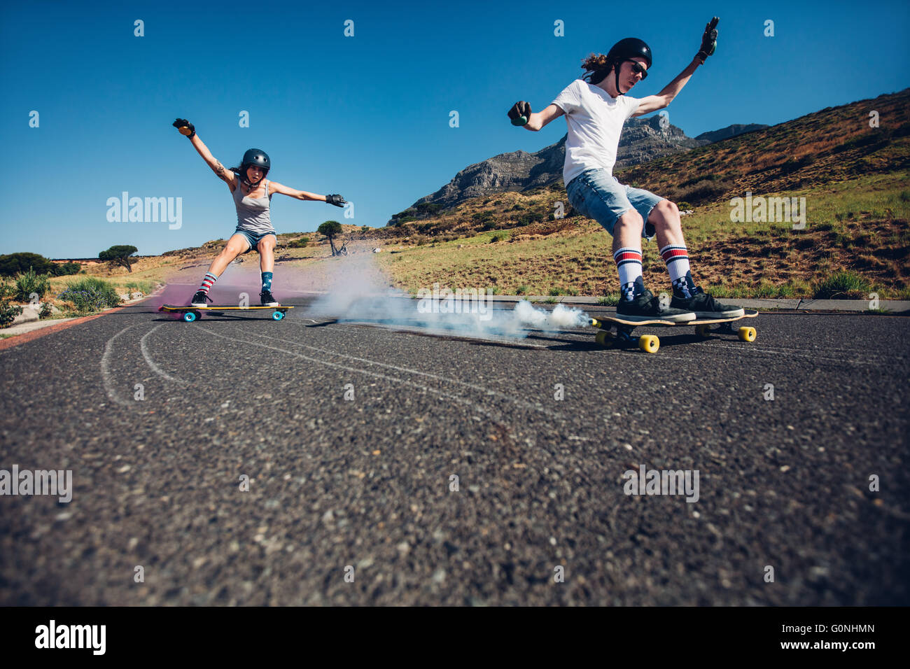 Full length shot of young man and woman outdoors longboarding down the road. Skate boards with smoke grenade. People - Stock Image