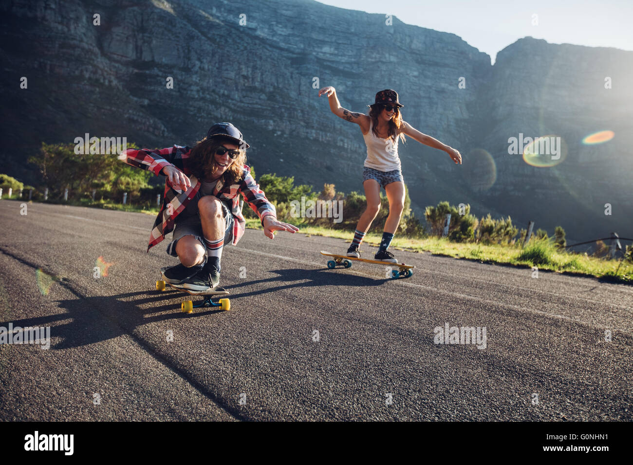 Happy young friends having fun with skateboard. Young man and woman skating together on a sunny day. - Stock Image