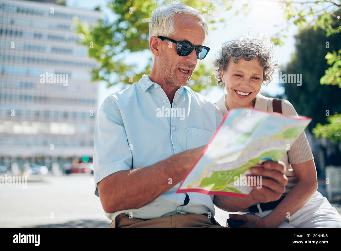Senior couple looking at city map. Mature man and woman sitting outdoors in city reading a map for direction. - Stock Image