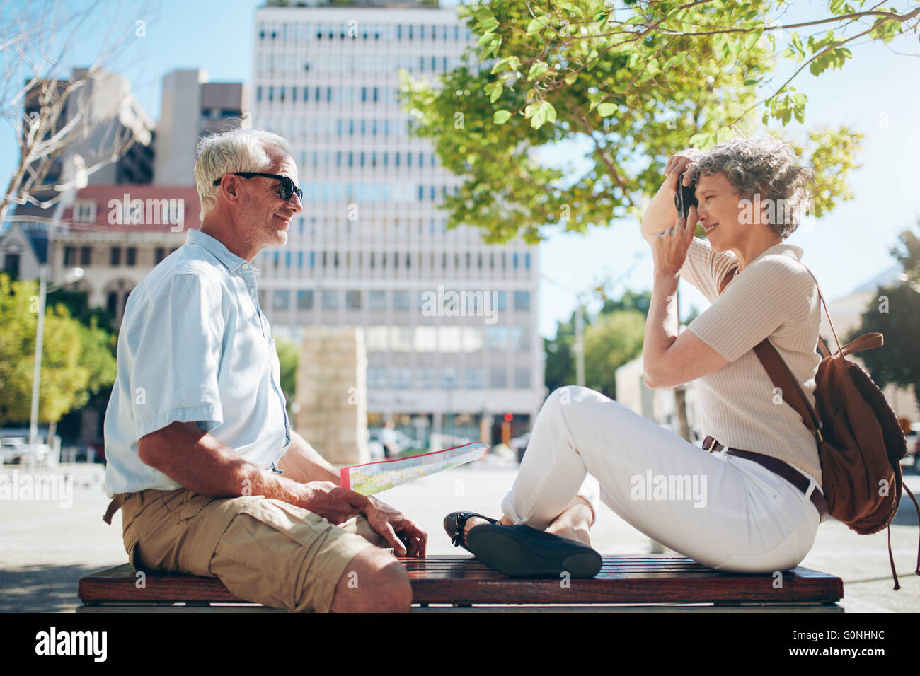 Side view of senior man sitting outdoors on a bench and woman taking his pictures with digital camera. Senior couple - Stock Image