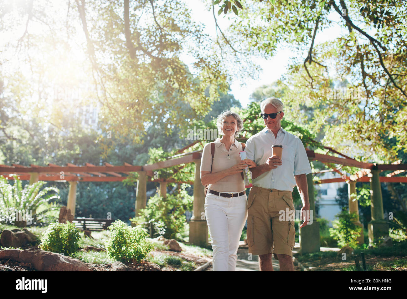 Portrait of couple of senior tourist walking through a park on a summer day. mature couple on a vacation. - Stock Image