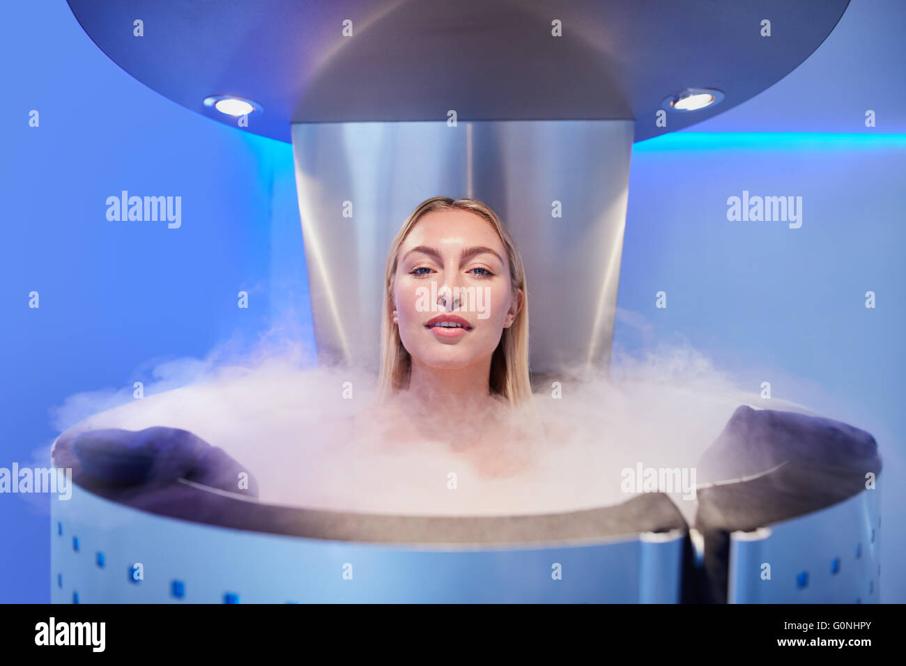Portrait of a beautiful young woman in cryosauna cabin for whole body cryotherapy. Caucasian female in freezing - Stock Image