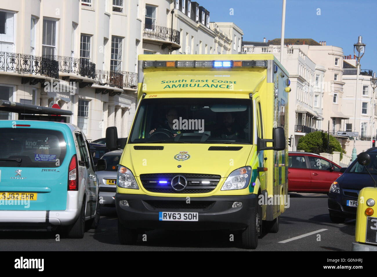 A SOUTH EAST COAST AMBULANCE IN TRAFFIC ON AN EMERGENCY CALL WITH BLUE LIGHTS FLASHING IN BRIGHTON - Stock Image