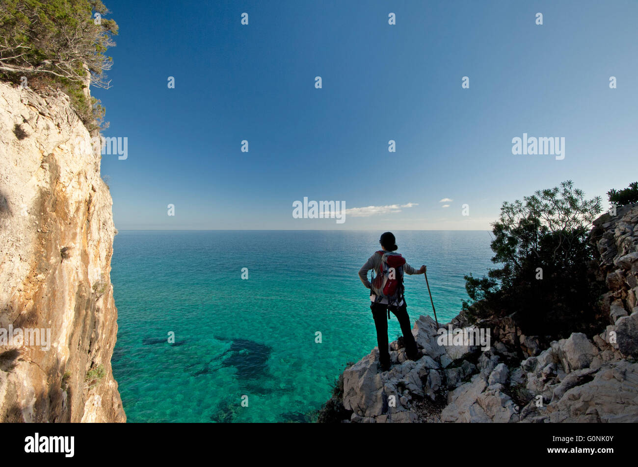 Baunei, Sardinia, Italy, 12/2015. Woman watching the sea along the famous Selvaggio Blu trekking route in the Ogliastra - Stock Image