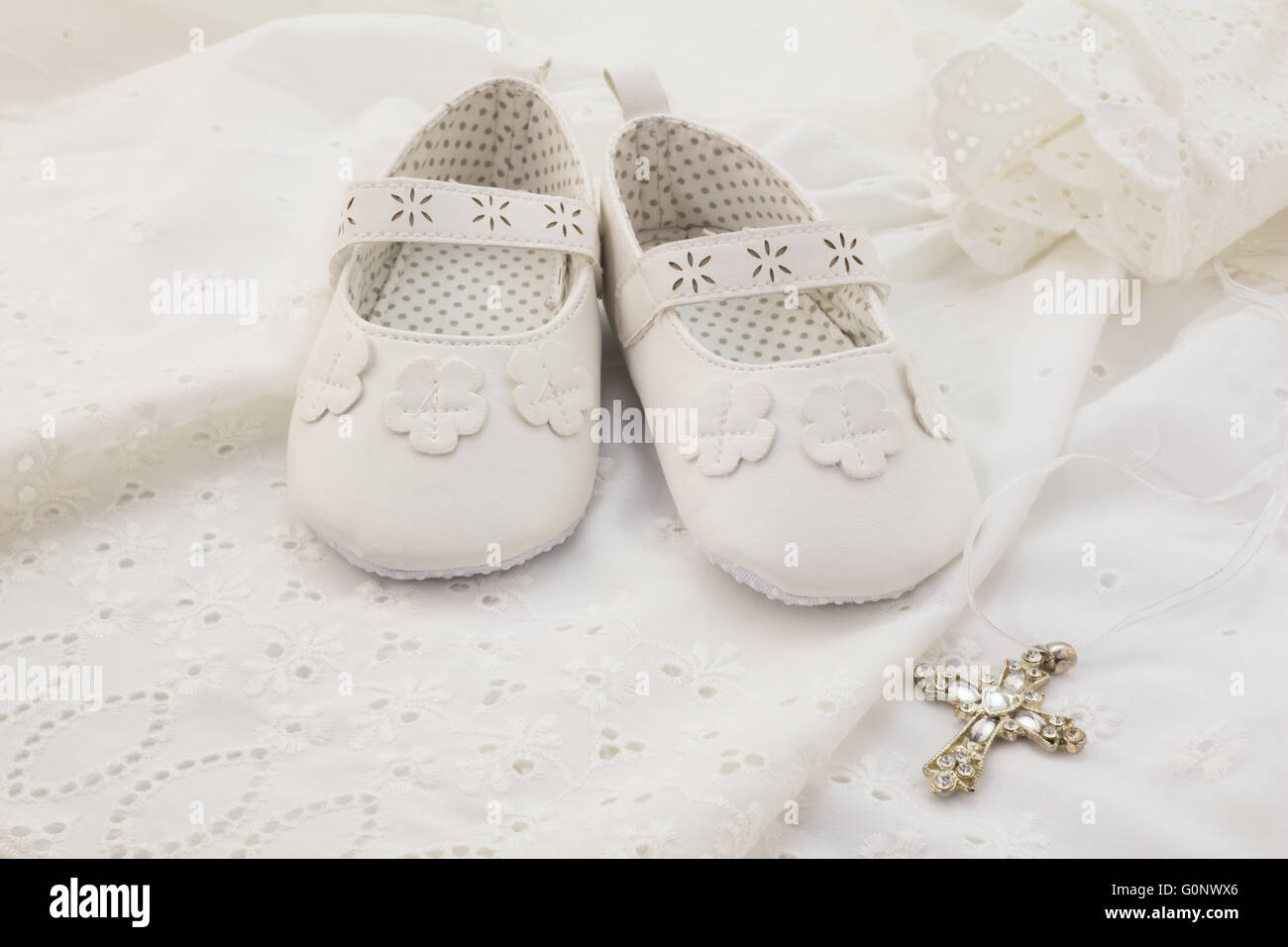 Baby christening white shoes with cross on white lace background - Stock Image