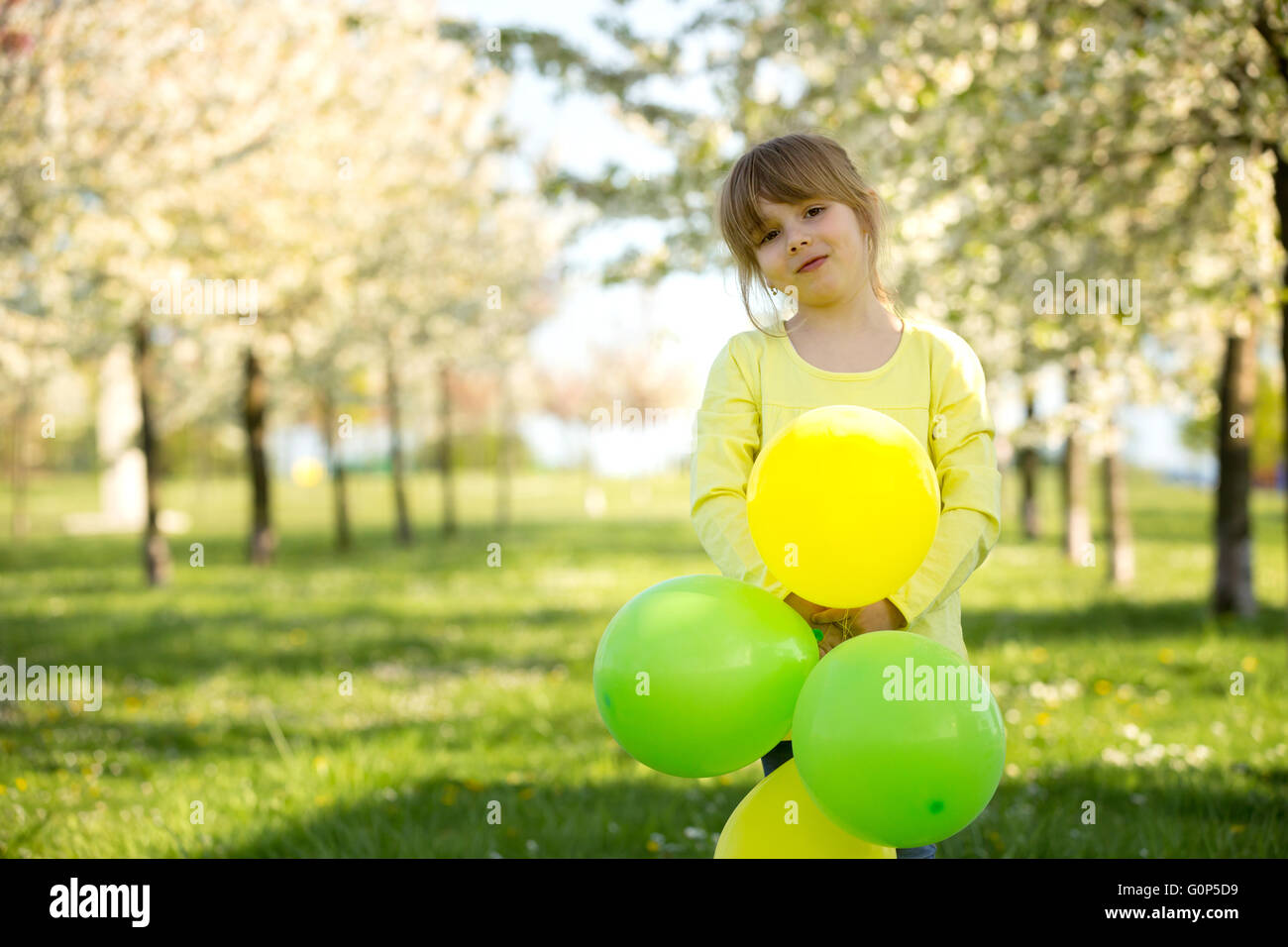 Cute little girl playing with balloons in a blooming apple tree garden, spring sunny late afternoon - Stock Image