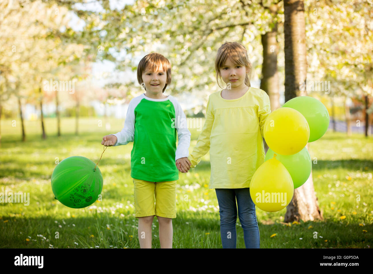 Cute little girl and boy, friends, playing with balloons in a blooming apple tree garden, spring sunny late afternoon - Stock Image