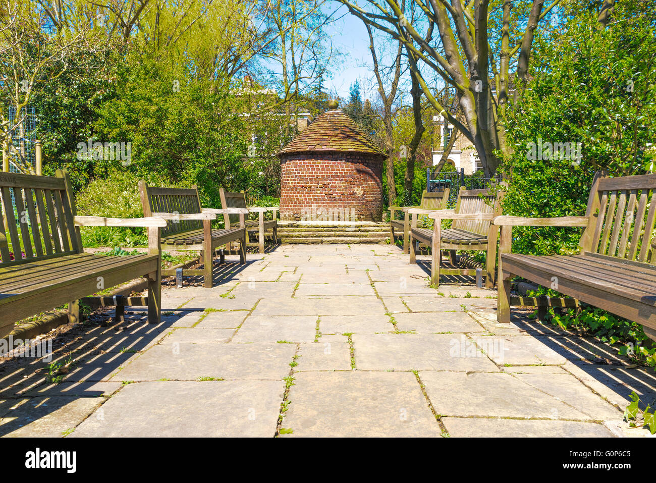 A small circular red brick hut and wooden benches in the sun at the New River Walk, Canonbury, London - Stock Image