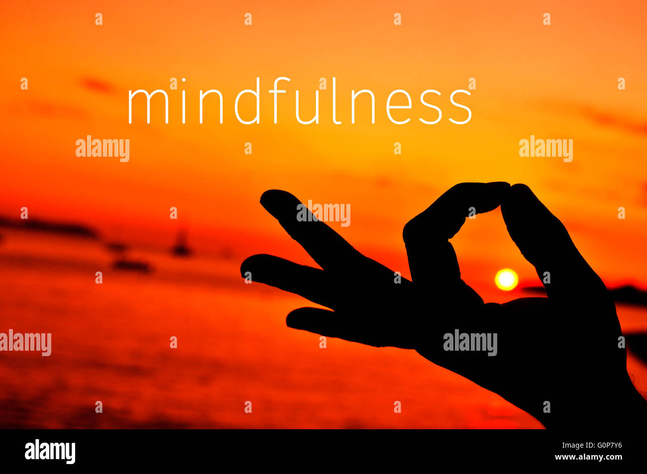 the text mindfulness and a closeup of a young man meditating with his hand in gyan mudra at sunset - Stock Image