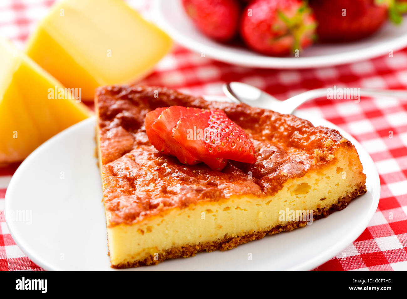 closeup of a plate with a piece of homemade cheesecake topped with sliced strawberry on a table set with a checkered - Stock Image
