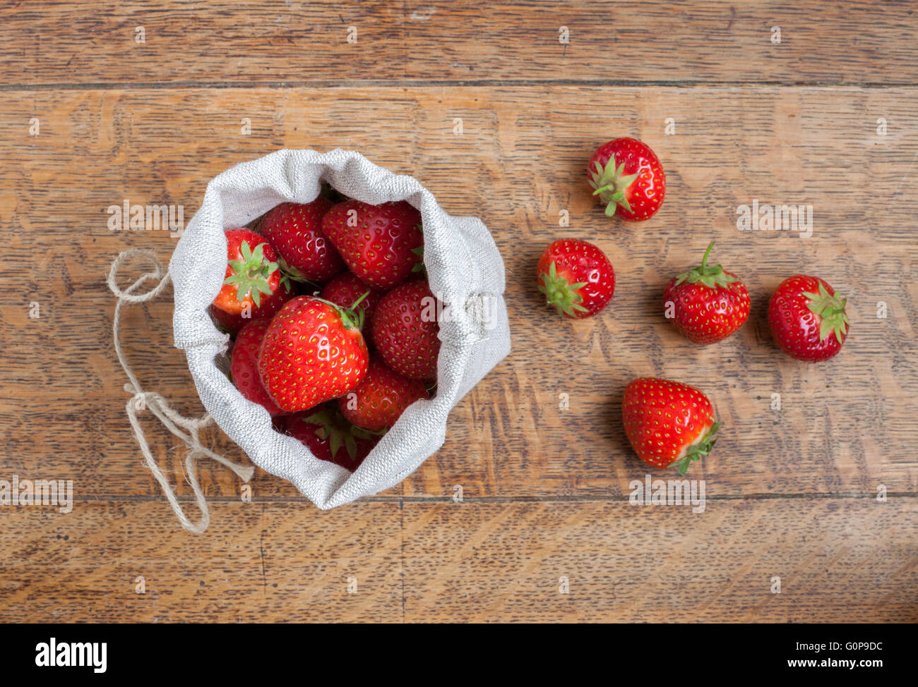 Overhead view of fresh strawberries in a small hessian bag on a wooden kitchen table with a loose strawberries beside - Stock Image