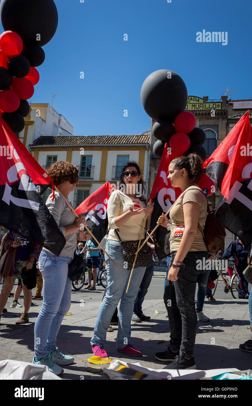 Young women talking together with black and red balloons and flags, as workers gather to protest in Seville on 1st - Stock Image
