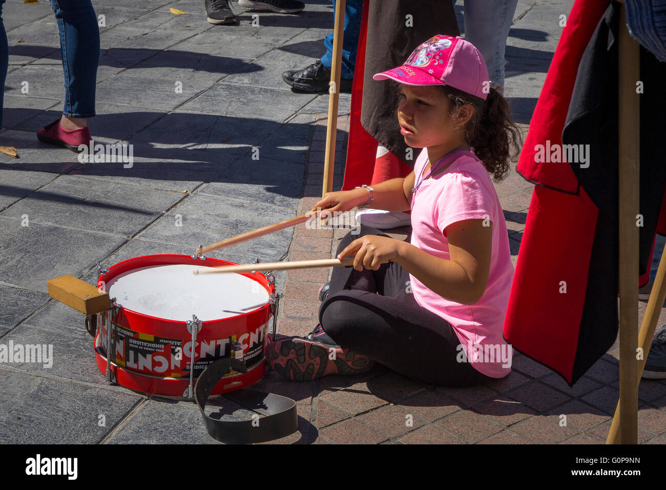 Small girl plays a drum at a workers' protest Mayday gathering in Seville on Sunday 1st May 2016. Protests included - Stock Image