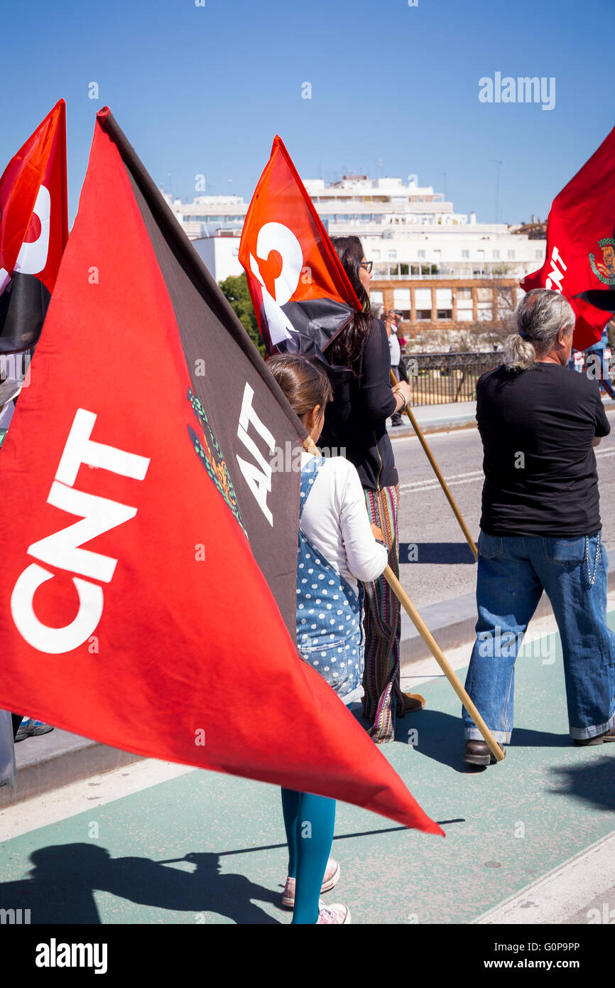 Young girl carrying black and red flag at a workers' Mayday protest march overTriana bridge (Puente de Isabel - Stock Image