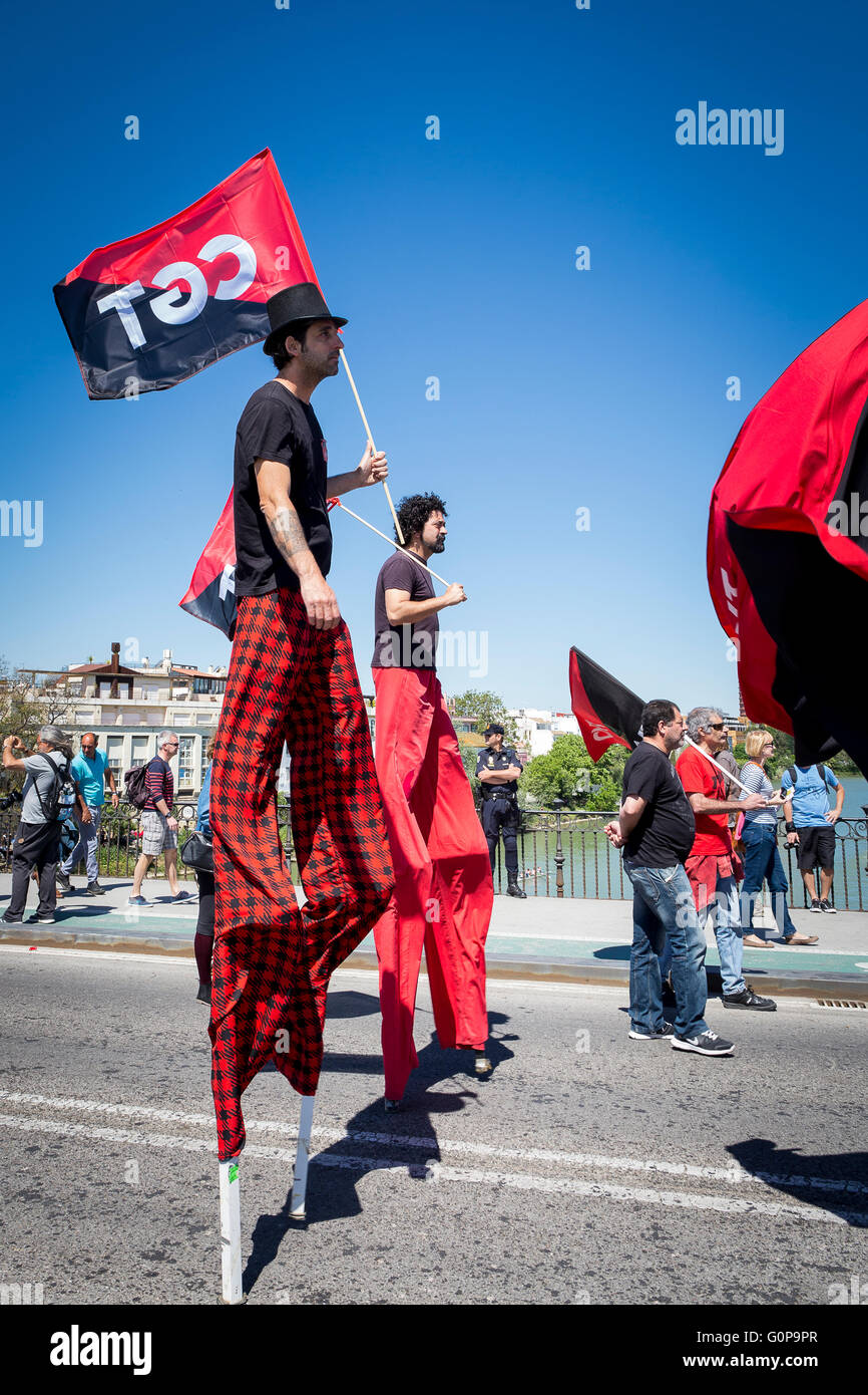 Men on stilts dressed in black and red, carrying black and red flags at a workers' Mayday protest march over - Stock Image