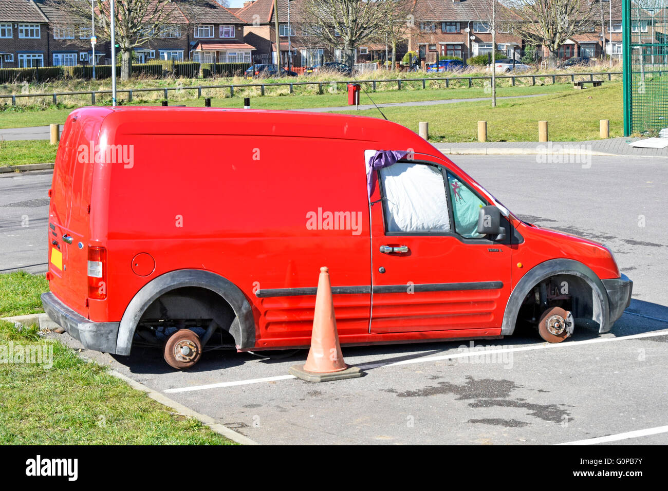 Vandalised red Ford Transit T230L van wheels removed possibly being used vagrants sleeping facility whilst 'parked' - Stock Image