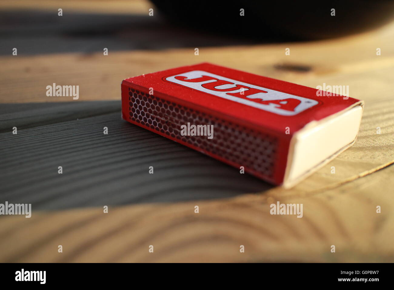 A small red box of 'Jula' matches, resting on a table in the evening sunlight. - Stock Image