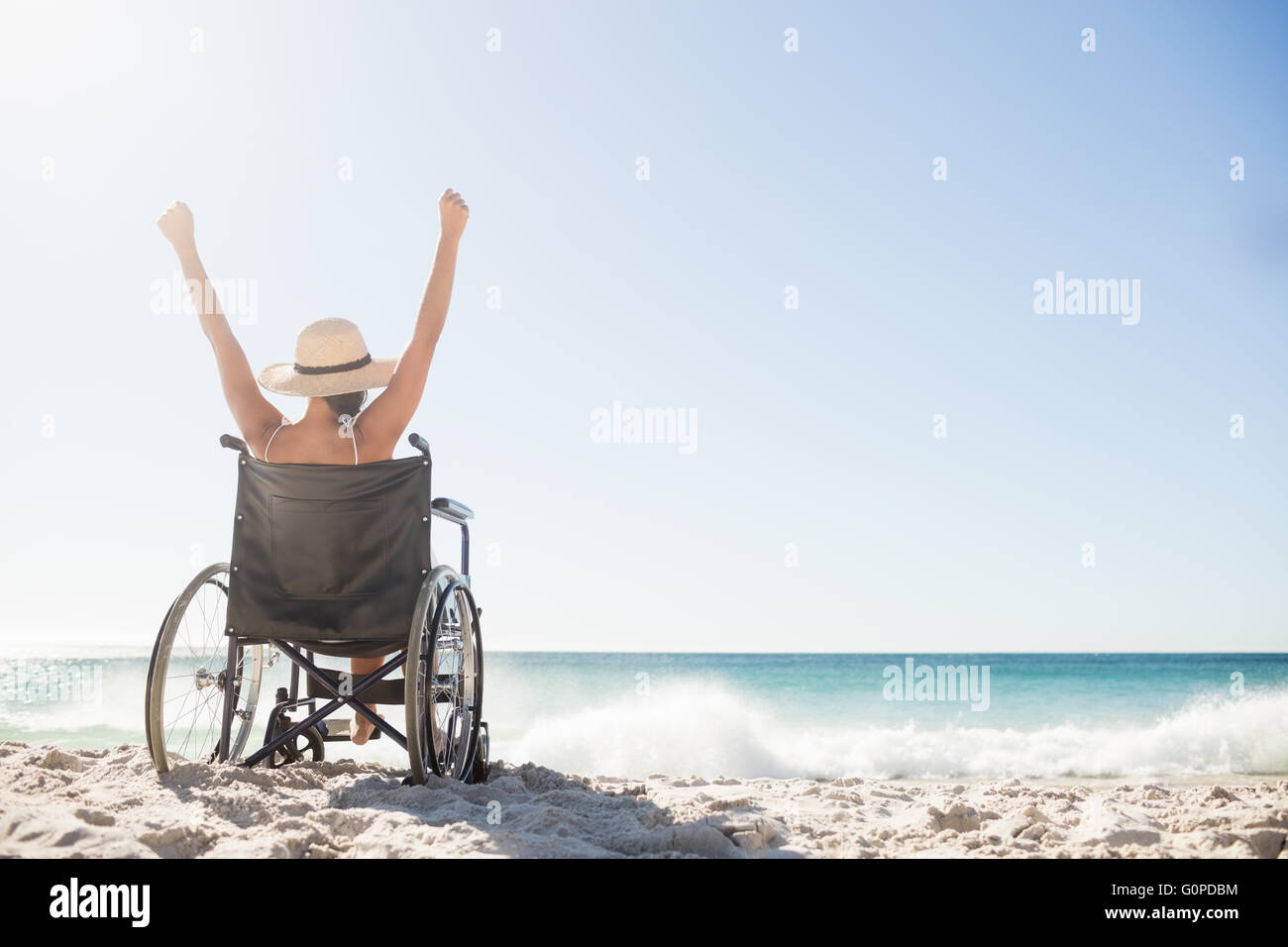 Wheelchair woman sitting  with arms up - Stock Image