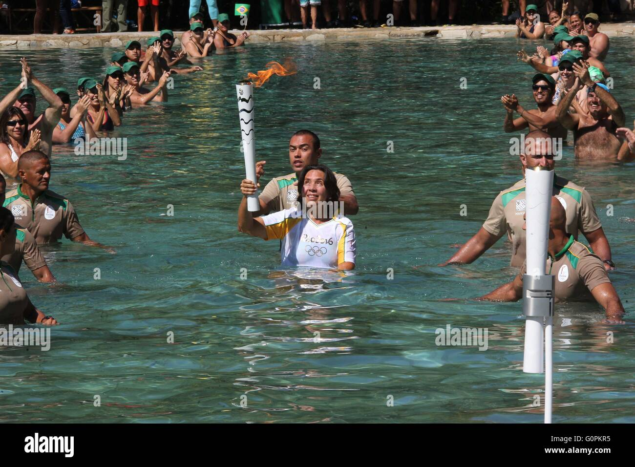 Brazilian torch runner, Flavia Canta, a public servant carries the torch across a swimming pool at the Brasilia - Stock Image
