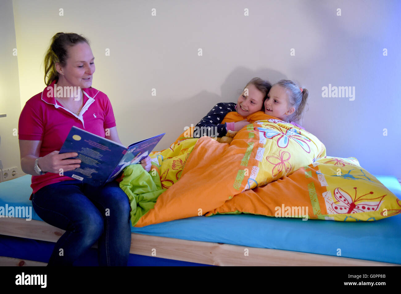 Sisters Skady-Lee (10) and Lucy-Mae (6) sit on a bed next to their mother Wiebke Ruedig at the night nursery at Stock Photo