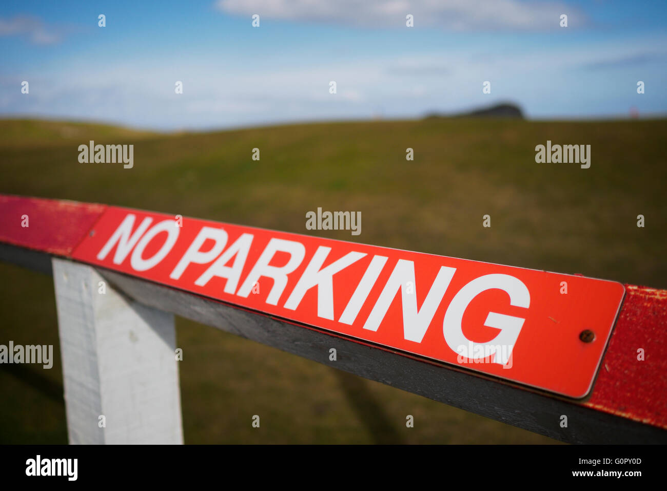 A red no parking sign on a wooden fence. - Stock Image