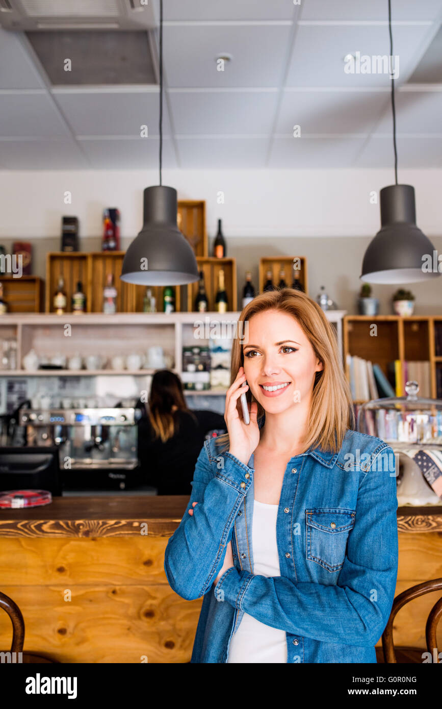 Blond woman standing at the bar, talking on phone - Stock Image