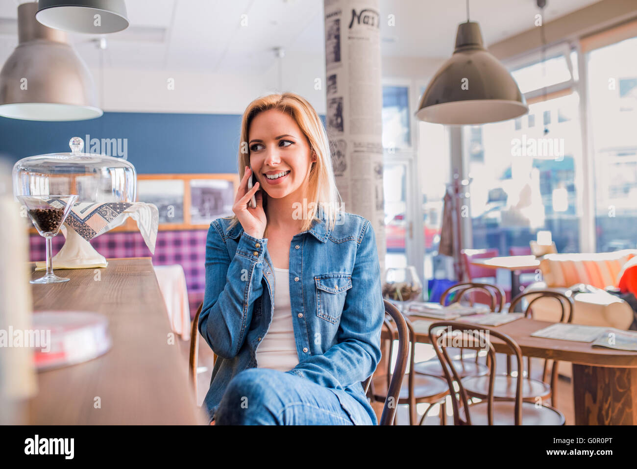 Blond woman sitting at the bar, talking on phone - Stock Image