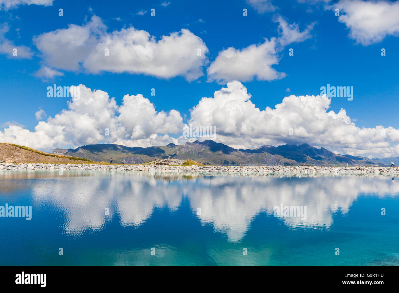 Stunning view of the Fallbodensee (lake) on Bernese Oberland with reflection of clouds and mountain ranges, Switzerland. - Stock Image