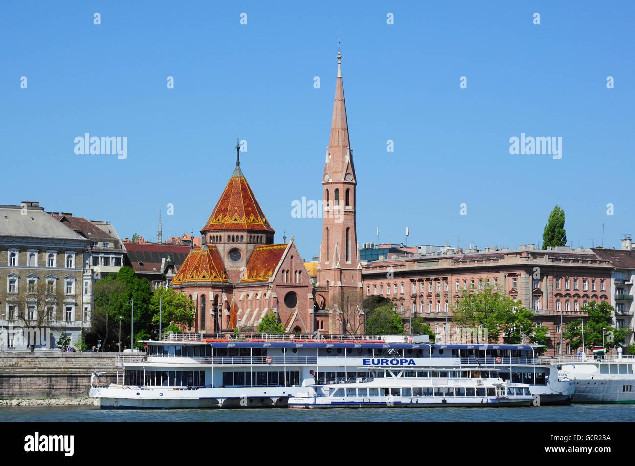 River Danube cruise ship and Buda Calvinist Church, Budapest, Hungary Stock Photo