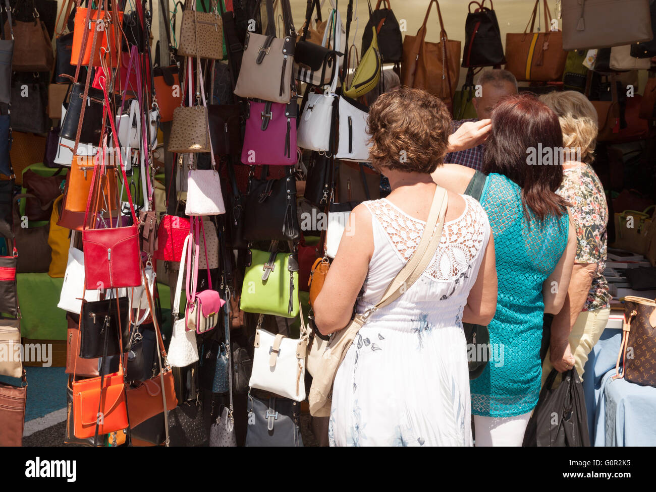 Women shopping for leather handbags at a market stall fcc76d04ffed6