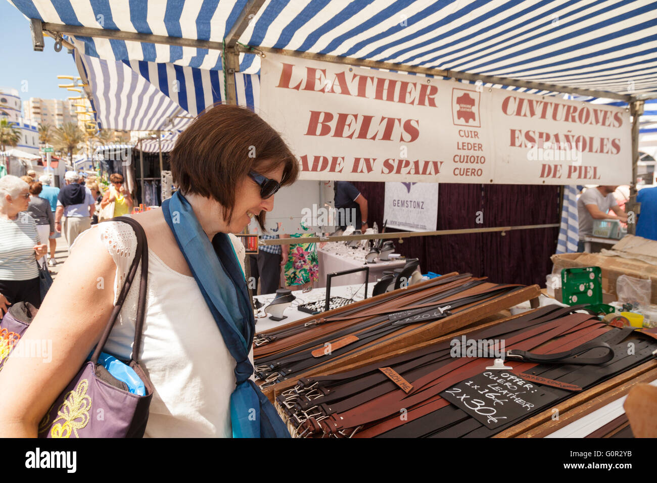 Woman buying leather belts at a leather belt stall, Estepona market, Costa del Sol, Andalusia Spain Europe - Stock Image