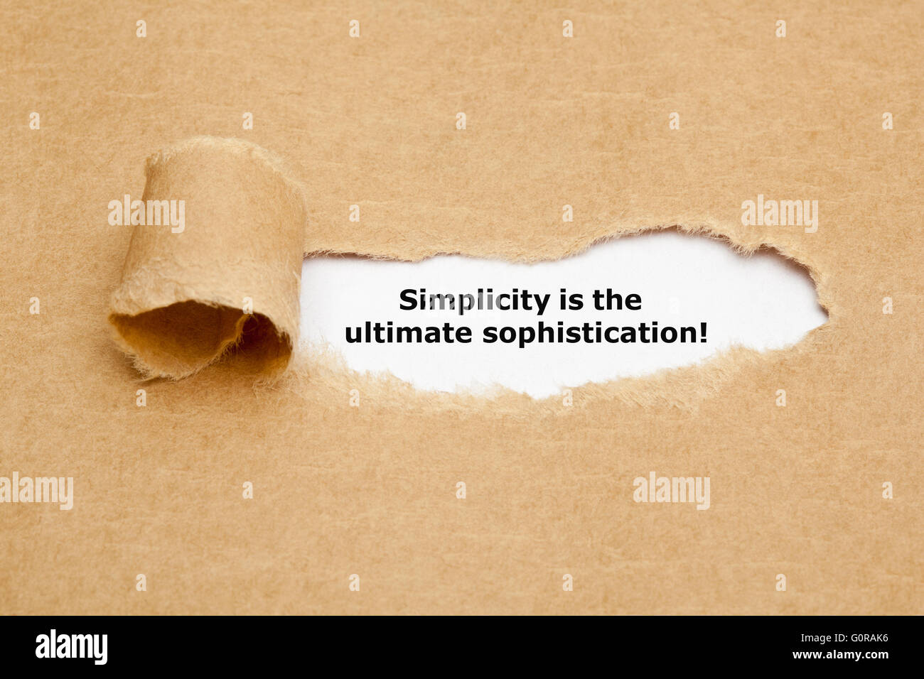 Motivational quote Simplicity is the Ultimate Sophistication, appearing behind torn brown paper. - Stock Image