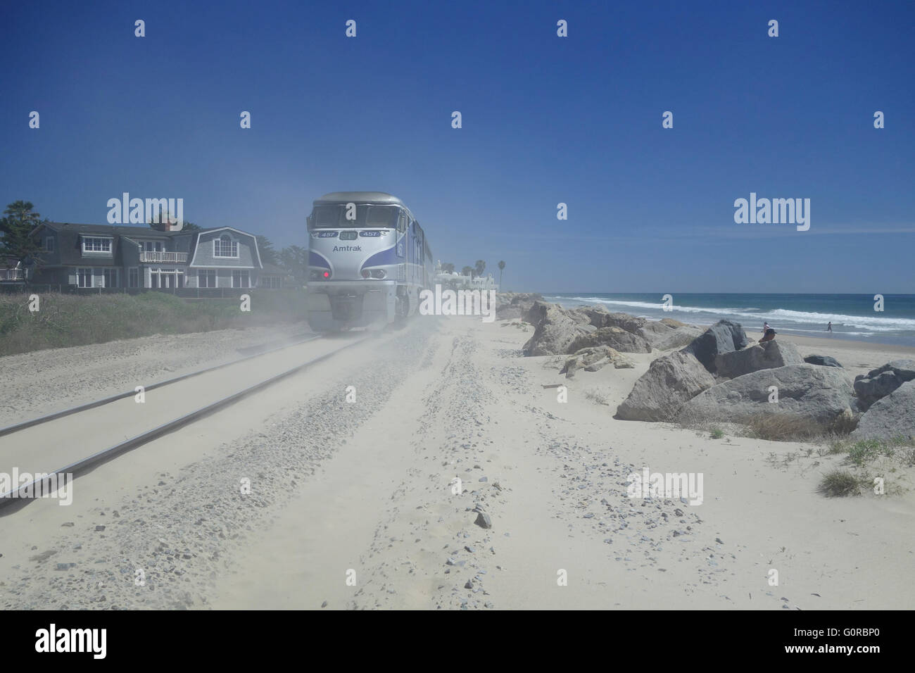 Amtrak Surfliner locomotive and passenger train on railroad tracks beside sandy beach near Santa Barbara Southern - Stock Image