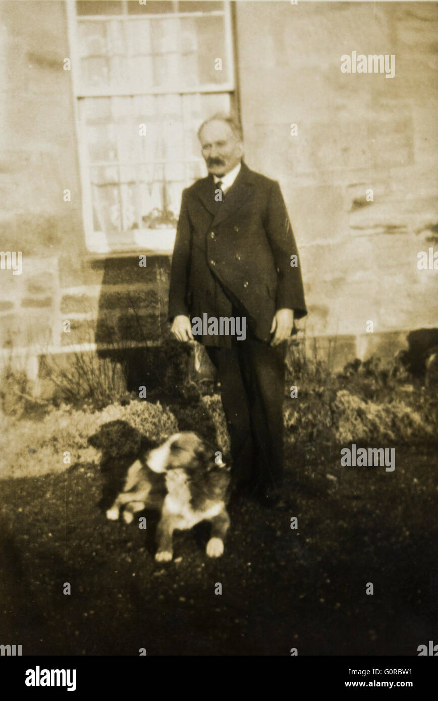 Historical Black and White Photograph man with dog posing - Stock Image