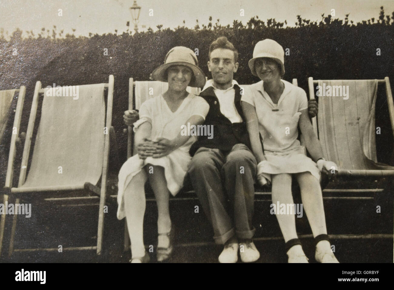 Historical Black and White Photograph Man and Two Woman sitting on deckchairs in summer - Stock Image
