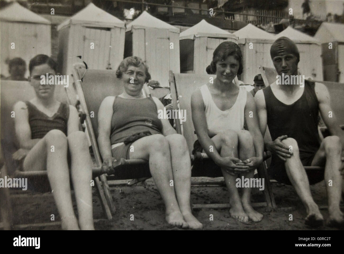10a5a44168b Historical Black and White Photograph People in Swimming Costumes sitting  on the Beach - Stock Image