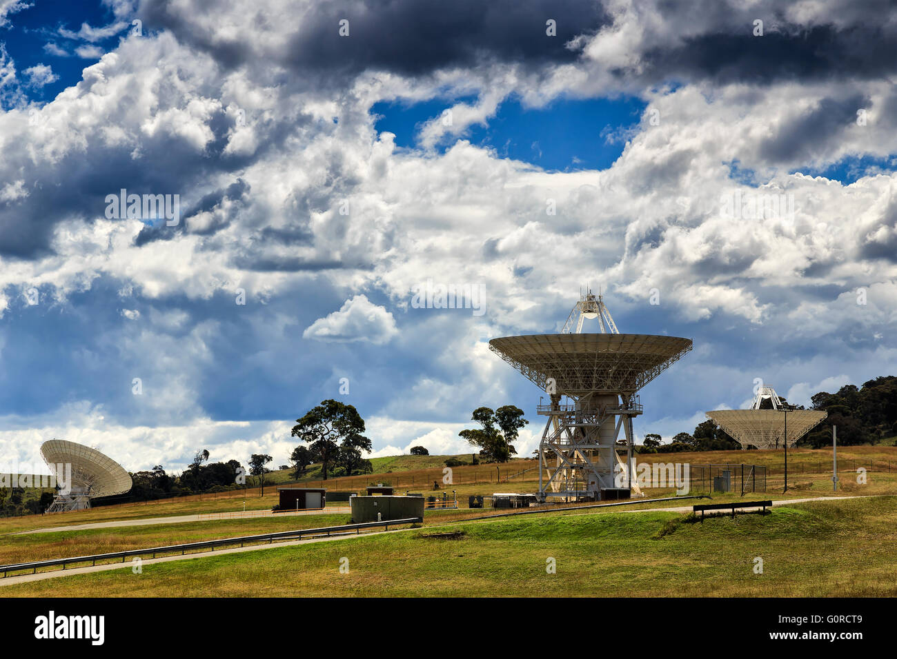 An array of satellite radio antenna dishes searching the signal and communicating with satellites from green hill - Stock Image
