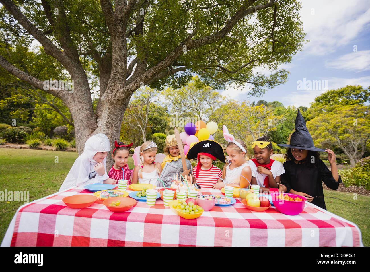 Children wearing costume having fun during birthday party - Stock Image