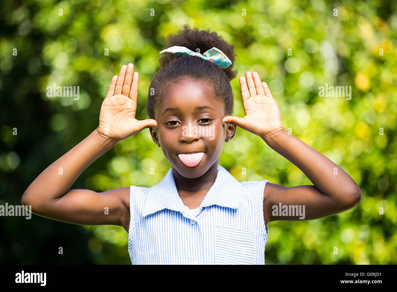 Cute mixed-race girl grimacing on a park - Stock Image