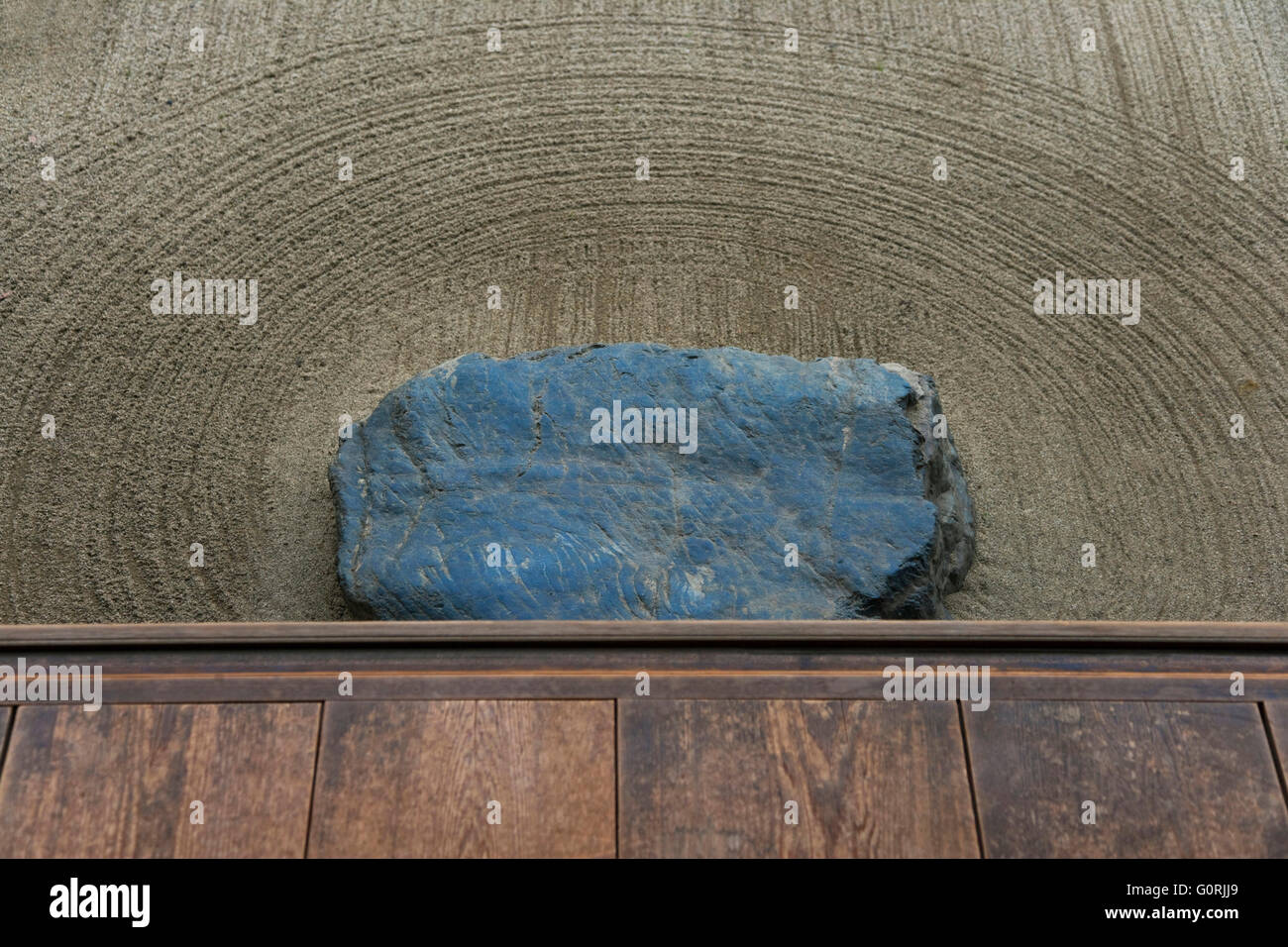A detailed view shows a shoe-removing stone in the carefully raked sand below the wooden engawa veranda at the edge - Stock Image