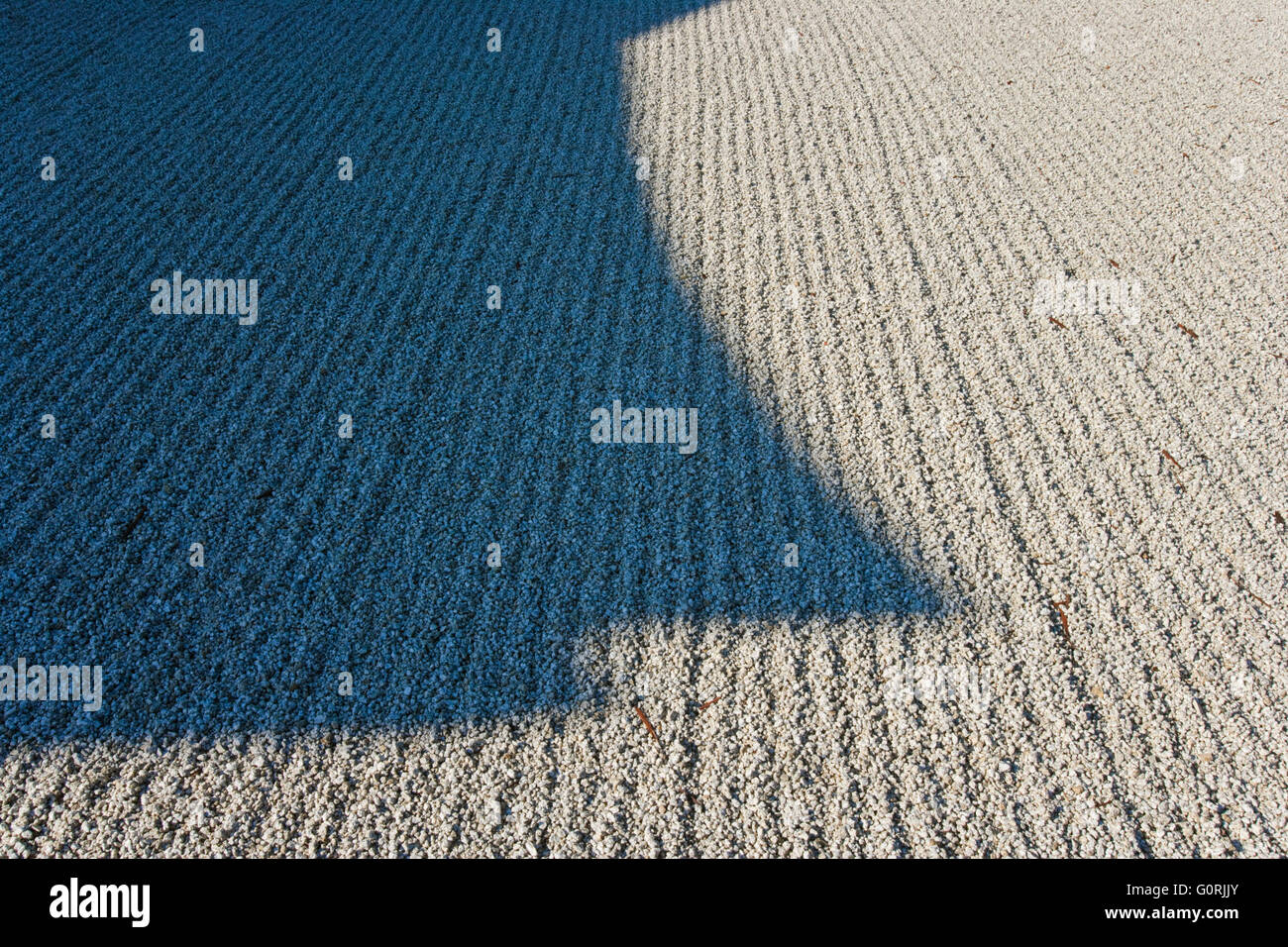 A shadow on a raked white gravel courtyard - Stock Image