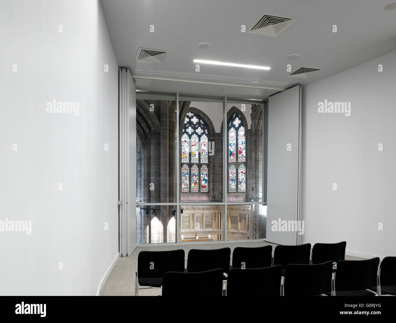 All Souls, Bolton, England. White room with rows of chairs. Stained glass windows. - Stock Image