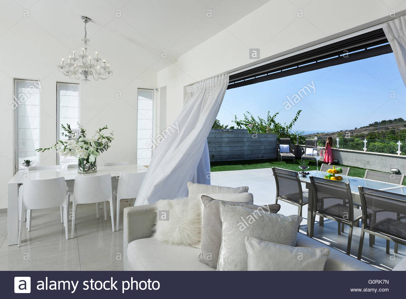 Villa in Haifa. View of modern living room and back patio. Glass ...