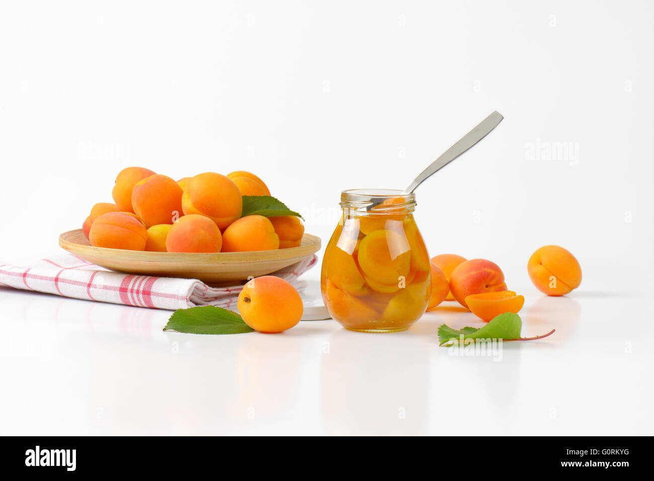 Jar of apricot compote and bowl of fresh apricots - Stock Image