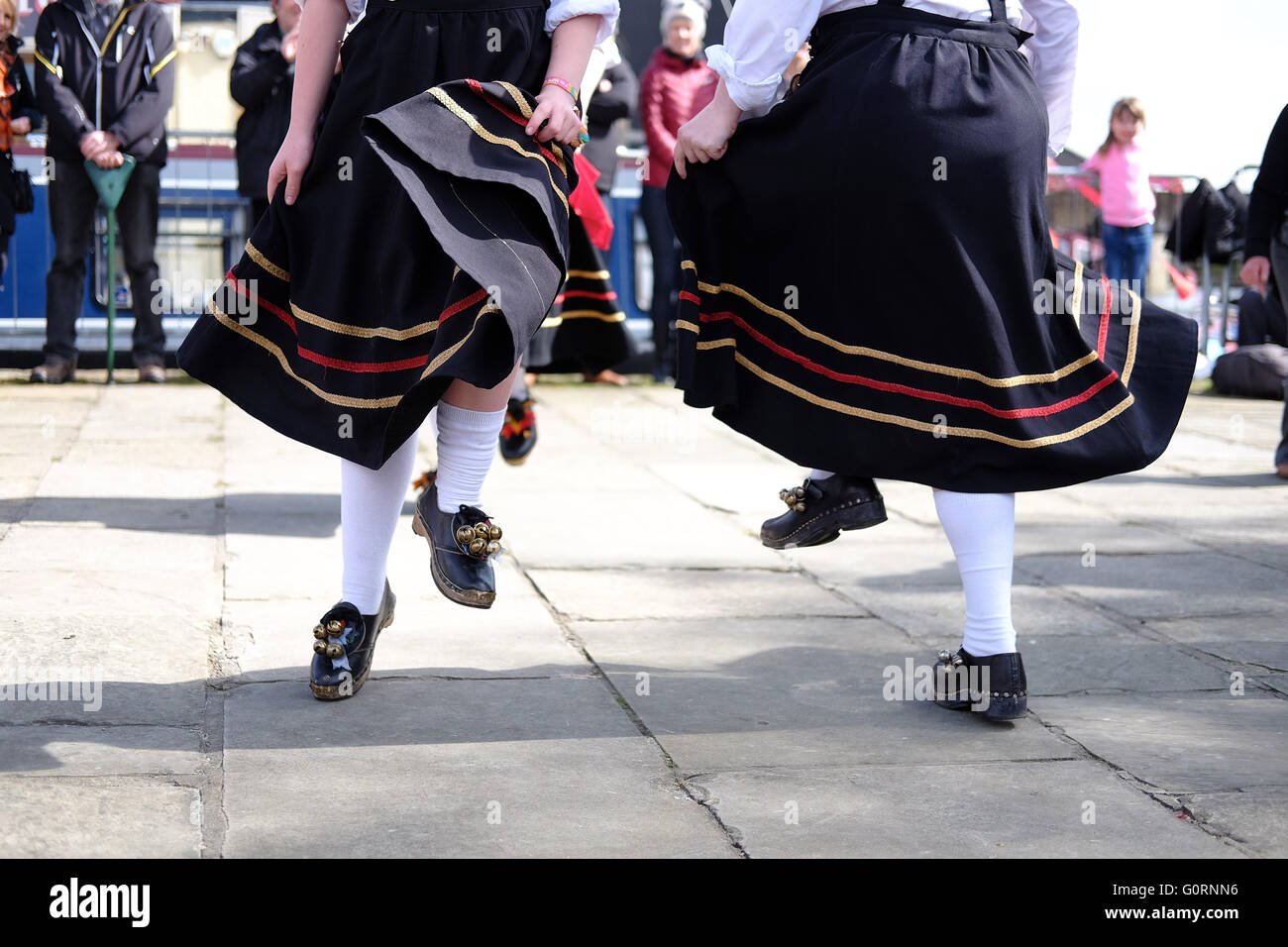 Feet of a morris dancing troop showing clogs and flowing dresses on a Yorkshire stone flagged pavement. - Stock Image
