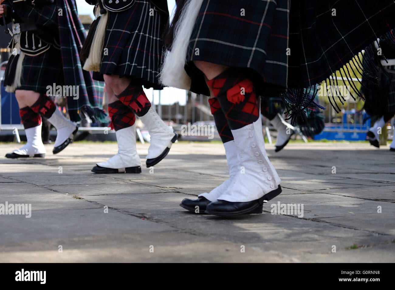 Low angle feet and leg shot of of three Scottish pipers with white spats, tartan socks and kilts. - Stock Image