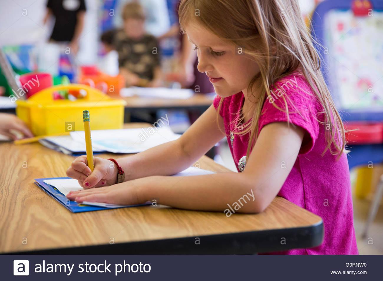 young girl in schoolroom working on classwork - Stock Image